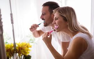 man and woman brushing teeth - how often should I brush my teeth